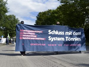 """Demonstrierende halten ein Banner mit der Aufschrift """"Schluss mit dem System Tönnies"""""""